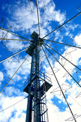 Communication Tower against puffy clouded blue sky