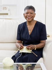 Mature African woman knitting on sofa at home