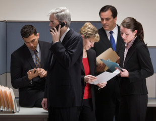Group of co-workers in crisis meeting in cubicle