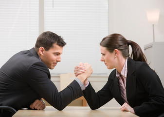 Co-workers aggressively arm wrestling for dominance
