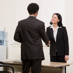 Confident woman shaking hands with co-worker in agreement