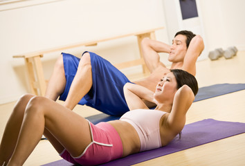 Man and woman doing stomach crunches in health club