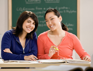 Student with text books doing homework with friend in school