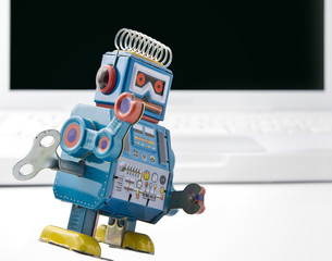 old retro robot toy and laptop