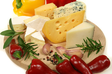 Cheese, peppers and herbs on a wooden board.