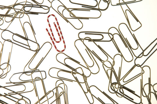 Rad and white paperclip in a group of metal paperclips