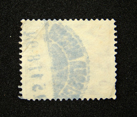 Blank postage stamp with postmark on black background