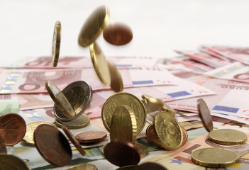 Euro coins falling on euro banknotes, isolated