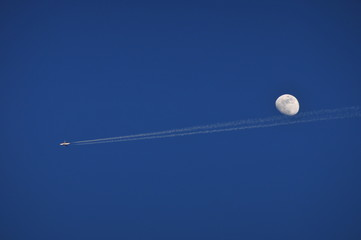 Contrail from a small plane underneath a full moon