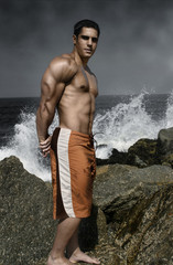 muscular guy on the rocks by the ocean