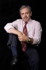 mature business man portrait on black background