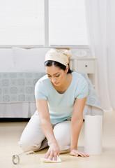Housewife kneeling in bedroom wiping up spilled water
