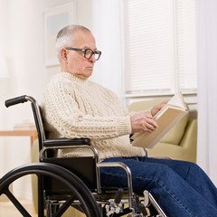 Disabled man in wheelchair enjoying reading a book
