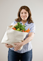 Woman holding grocery bag of fresh fruits and vegetables