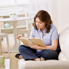 Relaxed woman sitting on sofa in livingroom reading book