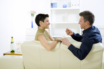 Man giving engagement ring to woman at home, smiling.