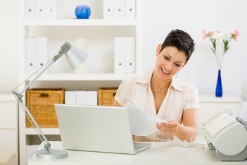 Business woman working on laptop computer at home.