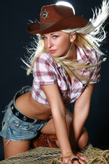 Blonde rodeo girl wearing a cowboy hat. Studio shot