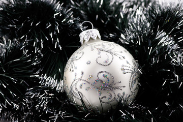 White Christmas bauble in green tinsel