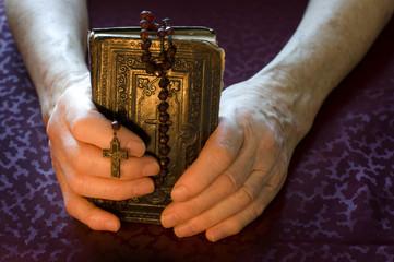 Frauenhände halten altes Gebetsbuch mit Rosenkranz