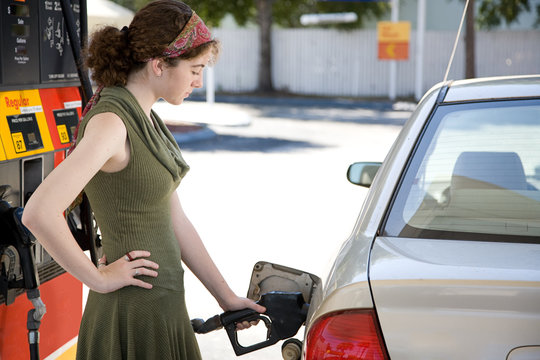 Teen girl at the gas station filling up the fuel tank car.