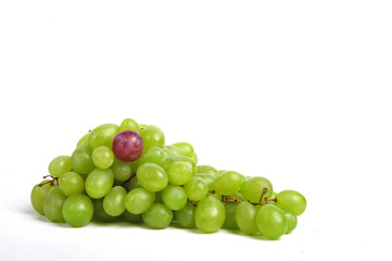 Cluster of white grapes with an outstanding red bean - close up