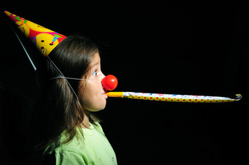 Portrait of a girl with party horn blowing in blowers