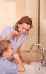 Child with mum clean a teeth in bathroom