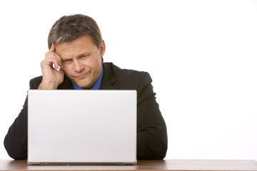 Businessman Frowning While Looking At Laptop