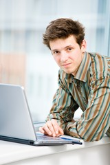 Casual looking businessman working on laptop computer