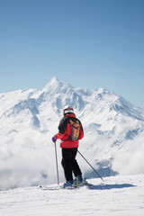Skier takes a break; in background the french alps, Europe.