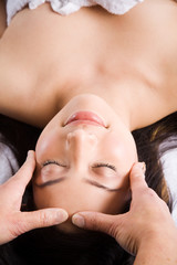A beautiful asian woman getting a massage in a spa salon