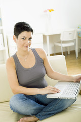 Young woman sitting on sofa at home working on laptop