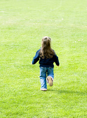 A young girl running across a large lawn