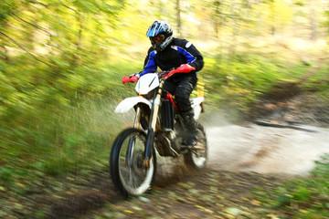 Offroad motorbike crossing river, water splashing. Motion blur.