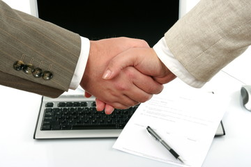 man and woman shaking hands in front of computer and document