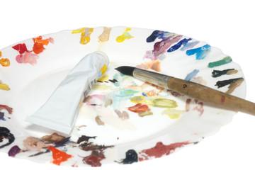 paintbrush, tubes of paint and porcelain plait as a palette