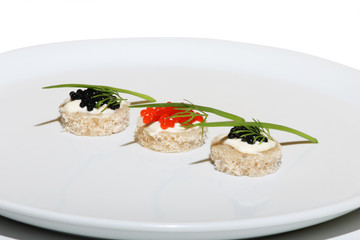 Black and red caviar on table with onion and dill