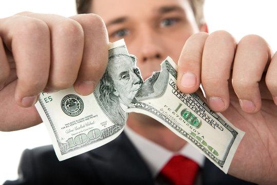 Close-up of human hands tearing hundred-dollar banknote