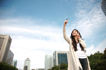 woman takes a self-photograph with a mobile telephone