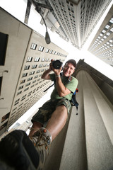 Fotobehang - Photographer in New York City. Wide angle view from below.