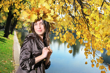 Wall Mural - Beautiful young woman in crown of golden autumn leaves in park.