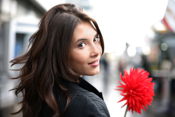 Beautiful woman with red flower looking back. Shallow DOF.
