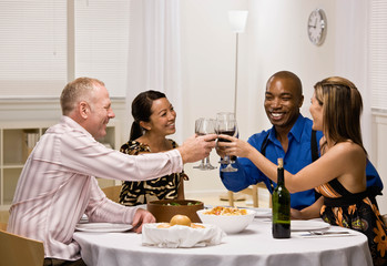 Happy couples toasting with red wine at elegant dinner party