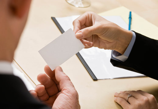 Businesswoman handing co-worker business card in meeting