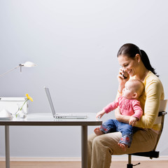 Working mother holding baby while talking on cell phone at desk