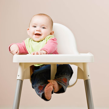 Happy, hungry baby in bib sitting in highchair