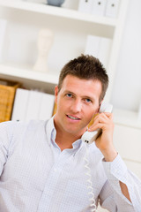 Business man working at home, calling on phone.