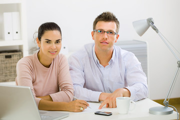 Couple working on laptop computer at home office, happy,
