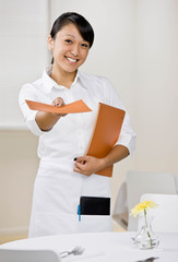 Happy waitress offering menu in elegant restaurant